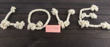 Love form with rope and the word end on wood background. royalty free stock images