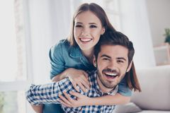 Love, friendship, trust, happiness. Beautiful couple of young lo. Vers are hugging indoors at home, looking at the camera, wearing casual clothes Royalty Free Stock Photos