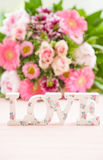 LOVE in front of flower bouquet Stock Images