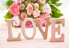 LOVE in front of flower bouquet Royalty Free Stock Photos