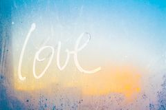 Love on the frozen glass. Word Love on the winter window Stock Photos