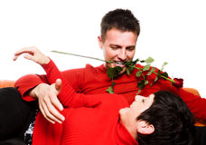 Love is fun. This is a happy moment. A young couple is having a date and the man tries to be very romantic and seductive. He keeps a rose between his teeth and Royalty Free Stock Images
