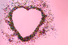 Love funny background. Heart in a frame of colorful sequins stars. Color confetti on a pink pastel trendy background. stock images