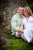 Love: Future Parents Sitting Beneath a Tree Stock Image