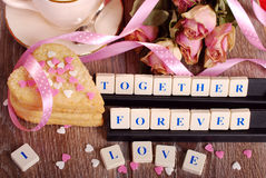 Love game. Love words made of scrabble letters ,dried roses  and heart shaped cookies with sprinkles  for valentine on wooden table Royalty Free Stock Photos