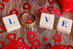 Love game. Love word made of scrabble letters and golden ring  for valentine on wooden table Royalty Free Stock Images