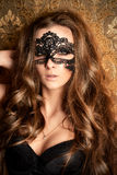 Love games. Beautiful young woman with long wavy hair wearing black lace mask. Carnival. Beauty, fashion stock image