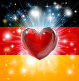 Love Germany flag heart background. Flag of Germany patriotic background with pyrotechnic or light burst and love heart in the centre Stock Photos