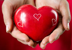 Love gift. Heart in female hands as a present Royalty Free Stock Photography