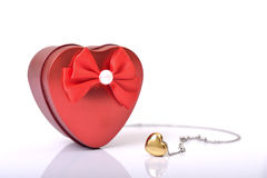 Love Gift Box. Red heart gift box and heart necklace on white background Stock Photo