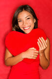 Love girl holding heart. Love concept photo with young woman in love holding red heart on red background. Multiracial asian caucasian valentines day woman Royalty Free Stock Photography