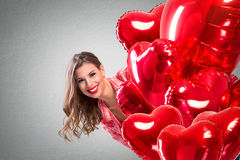 Love girl peeking behind a red balloons. Funny Valentine's Day Stock Photo