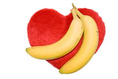 Love goes bananas. Two bananas on top of red heart with white background Stock Photo