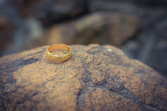 Love gold ring put on rock  vintage style Royalty Free Stock Photography