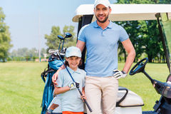We love golf!. Smiling young men embracing his son while leaning golf cart Stock Photos