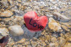 Love is gone. Red painted stone in the river lettered with love Stock Photography