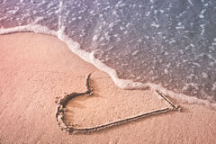Love goodbye. Heart drawn on the beach sand being washed away by a wave. Love affair, summer love or breakup and divorce concept. Ephemeral romantic love. Not Stock Images