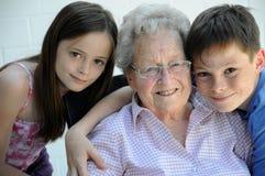 We love grandma. Grandchildren hugging their ninety years old grandmother Royalty Free Stock Photos