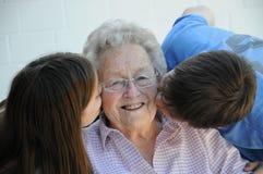 We love grandma. Grandchildren kissing their ninety years old grandmother Stock Photos