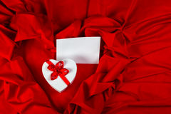 Love greeting card with heart on a red fabric. Love card. white greeting card and  heart with a red ribbon on a red fabric Royalty Free Stock Images