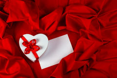 Love greeting card with heart on a red fabric. Love card. white greeting card and  heart with a red ribbon on a red fabric Royalty Free Stock Image