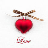 Love greeting card with red heart on the snow Stock Image