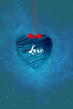 Love  Greetings. Blue heart hanged with dots and tied with red lace on blue glittering  background Stock Photography