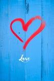 Love  Greetings. Love written below a heart on blue painted wood Stock Photo