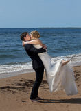 Love The Groom lifts his Bride as they kiss. The groom stands with his back towards the sea lifting his bride and she folds her arms around his neck and they Royalty Free Stock Photos