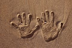 Love hand print with wedding rings on the sand Royalty Free Stock Image