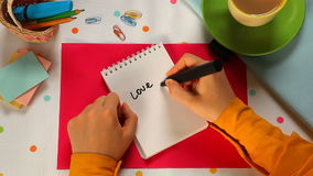 Love, hand writing word with heart in notebook as Valentines day concept stock video footage
