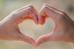Hand on heart-shaped bokeh background blurred natural tones vintage style. Show the world you love Love Family between two people. stock photos
