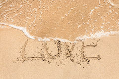 Love handwritten in sand for natural Stock Photo
