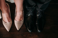 Love and happiness on wedding day. Closeup of bride`s and groom`s feet and shoes and wooden decoration `love` in their hands. Stock Photos