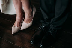 Love and happiness on wedding day. Closeup of bride`s and groom`s feet and shoes and wooden decoration `love` in their hands. Royalty Free Stock Photos
