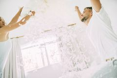 Love happy couple in the bedroom with feathers royalty free stock photography
