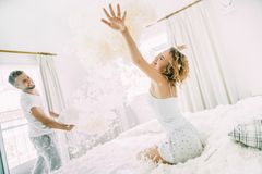 Love happy couple in the bedroom with feathers stock images