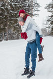 Love - Happy couple having fun smiling happy laughing together on romantic holidays. Young man giving piggyback ride to Stock Image
