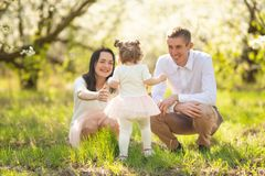 Love, happy family on vacation in a blooming garden in spring, summer. Cheerful mood and warm atmosphere.  stock image