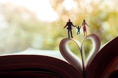 Love and Happy Family. Work Life Balance Concept. Miniature of Father, Mother and Son holding Hands and Walking toward the Book royalty free stock photo