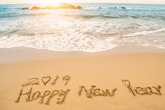 Love Happy new year 2019. Word 2019 happy new year and lover feet write on beach Royalty Free Stock Photography