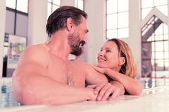 Happy positive couple swimming in the pool together royalty free stock photography