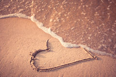Love has gone. Heart drawn on the beach sand being washed away by a wave. Toasted sand tone. Love affair, summer love or breakup and divorce concept. Ephemeral Royalty Free Stock Photography