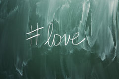 Love hashtag symbol. Handwriting on green blackboard Stock Images