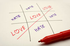Love and Hate. A Game of Tic-tac-toe showing the Love as a winner and hate as looser Stock Images