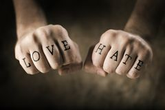 Love and Hate. Man with (fake) Love and Hate tattoos on his hands royalty free stock photography