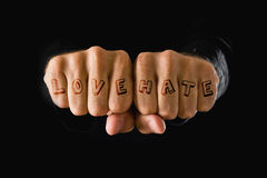 Love and hate tattooes, hands clenched in fist Royalty Free Stock Images