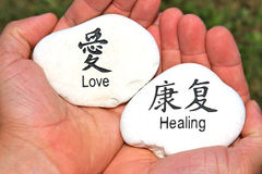 Love and Healing Stones. Concept of healing hands holding stones engraved with the words love and healing portrays the ancient spiritual traditions which are royalty free stock images