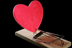 Love and health as a mouse trap. Metaphor with red candy heart Stock Photo