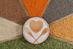Love healthy food concept with colorful grains and seeds surrounding wooden board stock photos